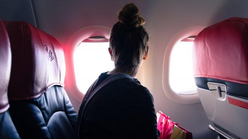 Mulher olhando janela de avião